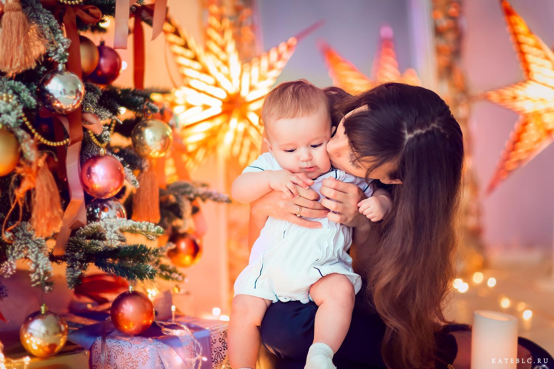 Мама и малыш у елки на фоне гирлянд