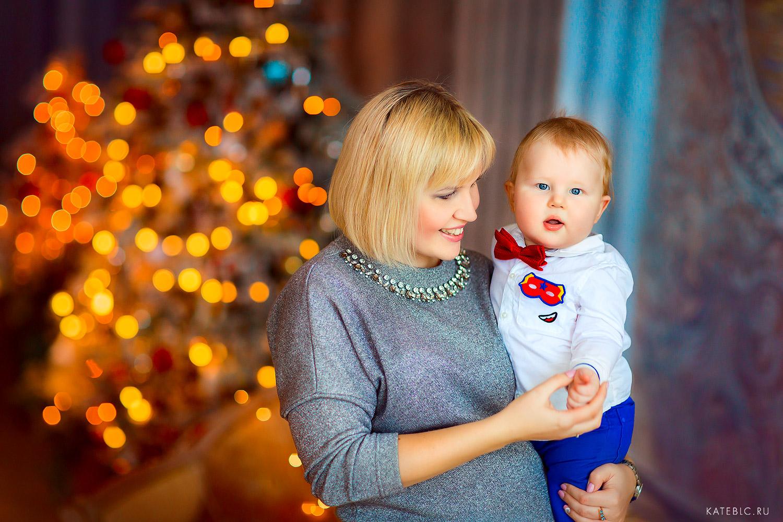 Мама и сын на фоне елки. детская фотосессия для малышей до года
