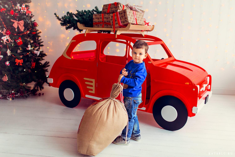 Мальчик у машинки с мешком подарков. Детская новогодняя фотосессия в студии