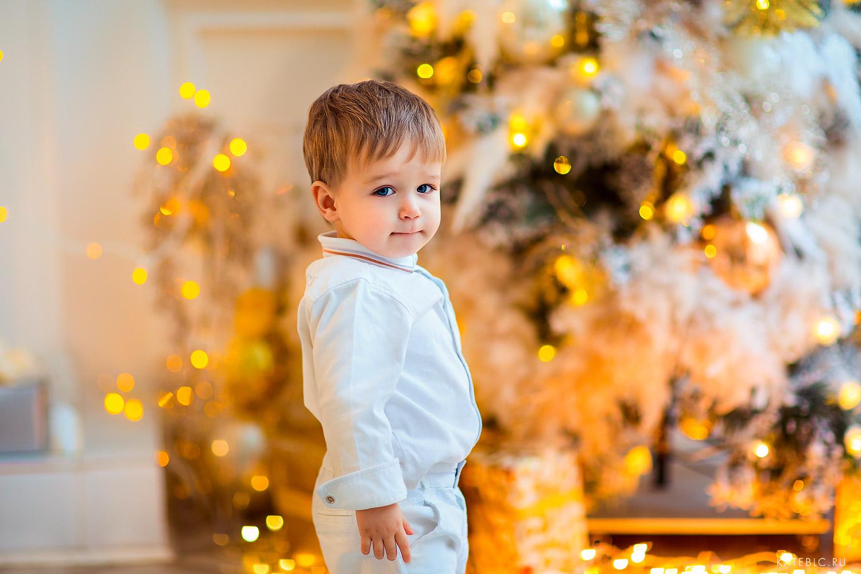 малыш возле елки. новогодняя фотосессия в студии