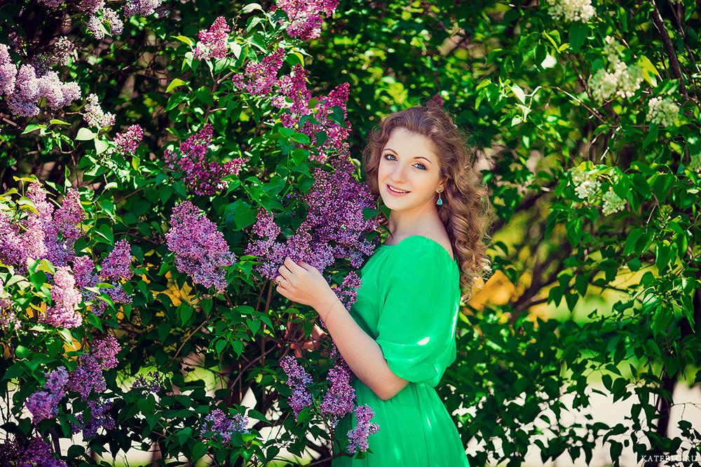 Девушка в зеленом платье в кустах сирени