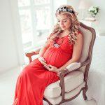 Фотосессия беременности в студии. Беременная девушка сидит на кресле в светлой фотостудии. Фотограф для беременных Катрин Белоцерковская
