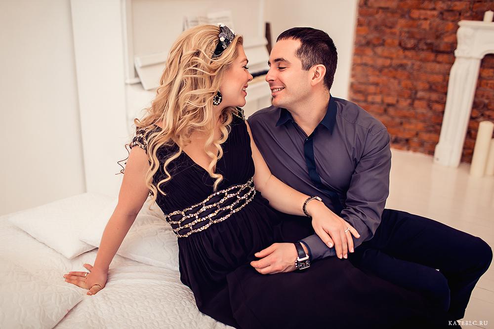 Фотосессия беременности в студии с мужем. Влюбленная пара на кровати.