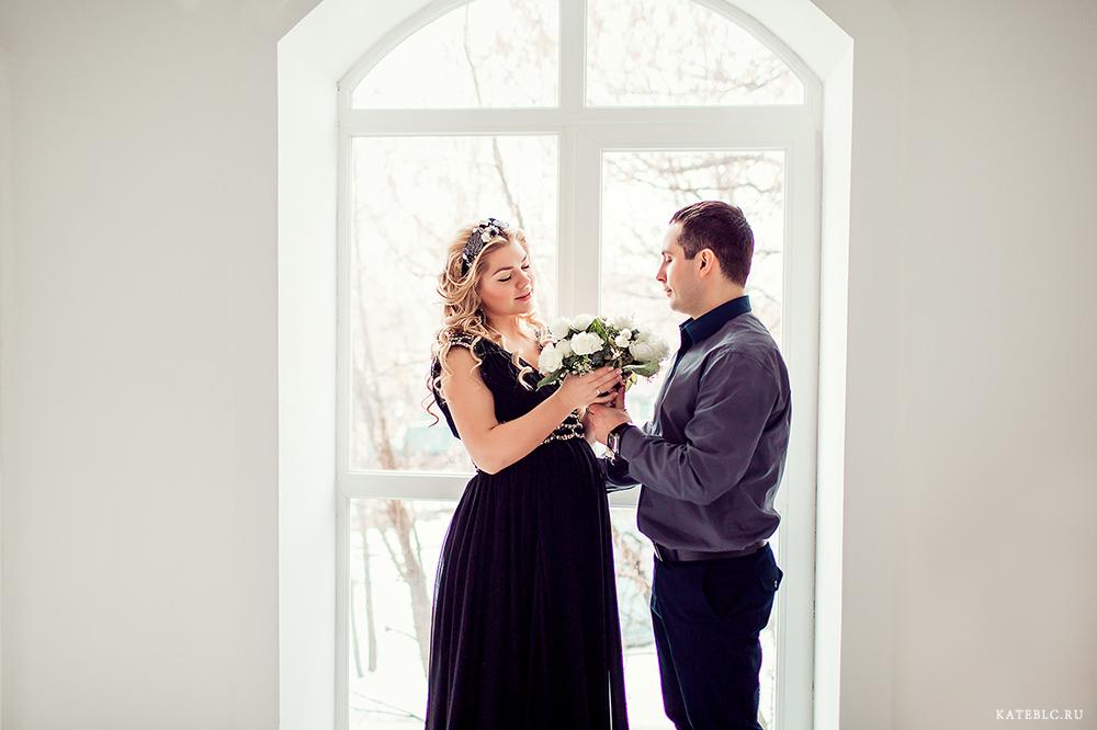 Фотосессия с цветами у окна в студии. Муж и жена на фотосессии в ожидании чуда в Москве