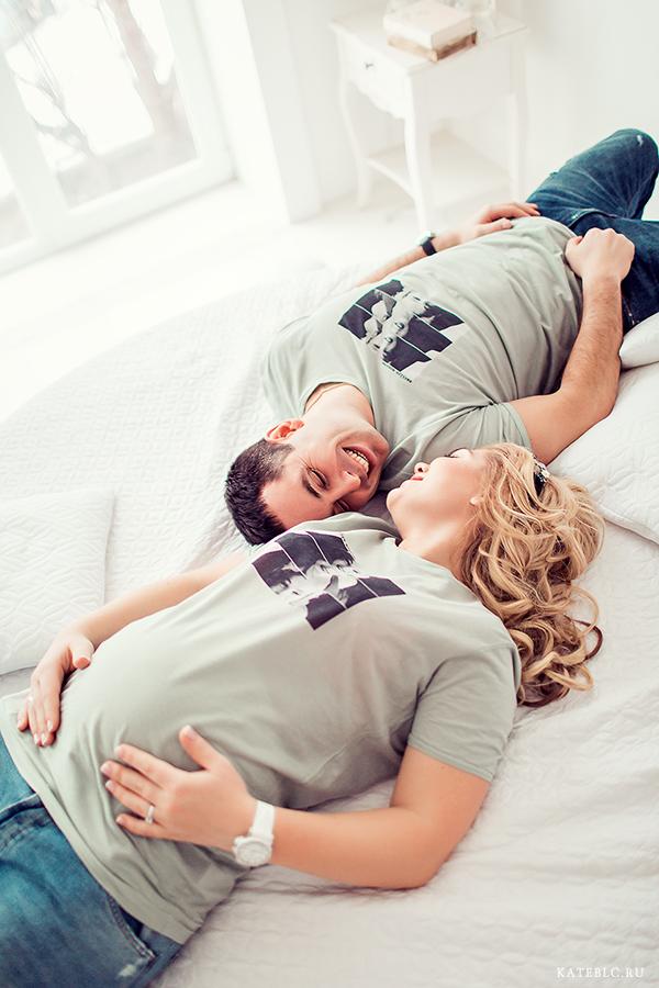 Муж и жена на кровати. Фотосессия беременности в студии