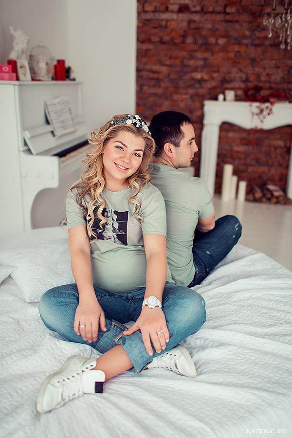 Беременная девушка с мужем на кровати в светлой фотостудии. Kate BLC Photography