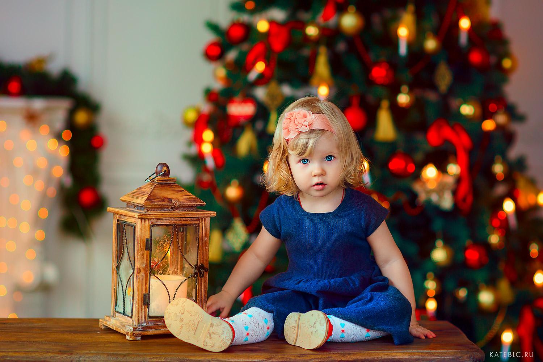 Девочка у елки в фотостудии. Фотосессии для детей. Семейный фотограф Катрин Белоцерковская kateblc.ru