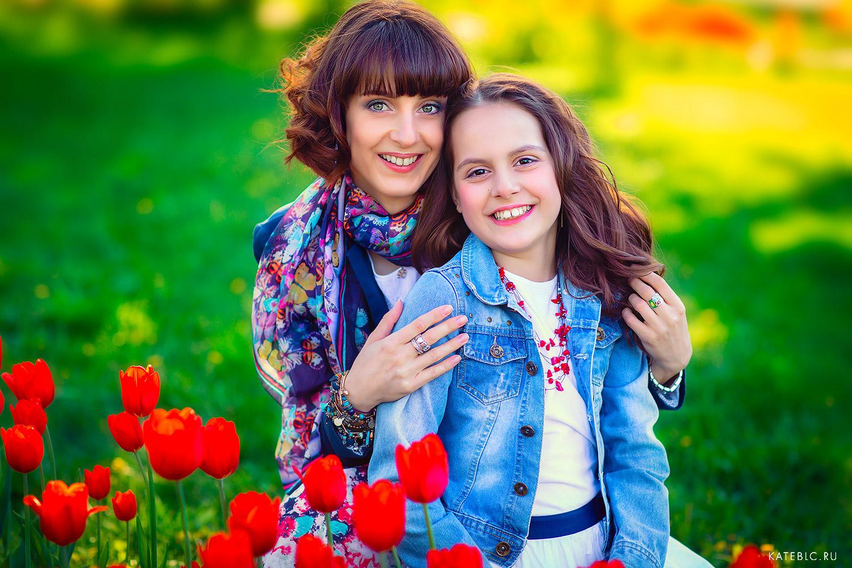 мама и дочка в цветах сидят на траве. Счастливые эмоции