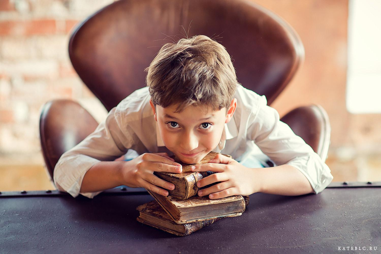 Мальчик за столом с книгами. Детская фотосессия в студии