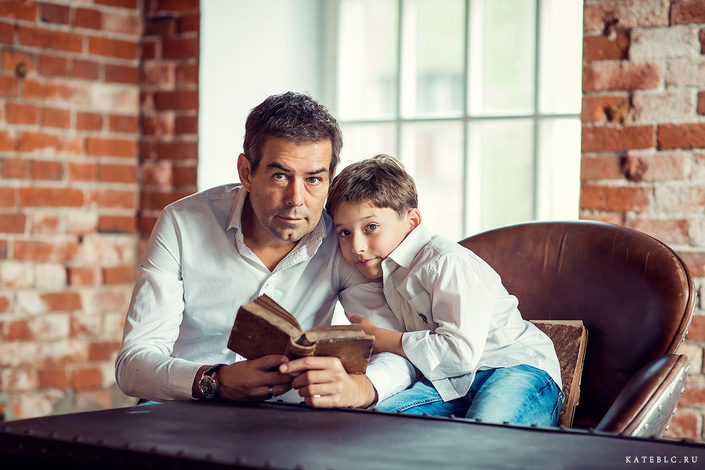 Папа и сын за столом с книгой. Семейная фотосессия в студии. Фотограф Катрин Белоцерковская